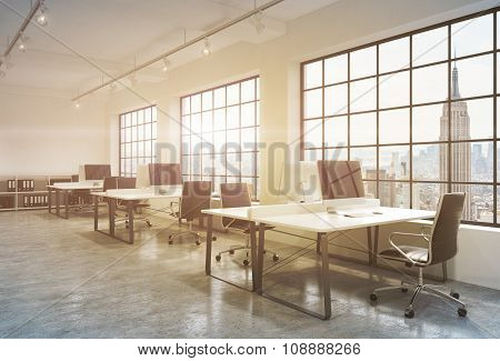 Workplaces In A Sunset Loft Open Space Office. Tables Are Equipped With Computers; Book Shelves. New