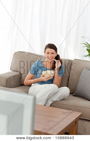 Woman Laughing While Watching A Movie On Television In The Living Room