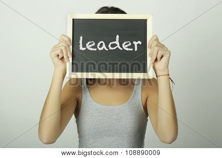 Young Woman Holding A Chalkboard Saying Leader.