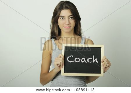 Young Woman Holding A Chalkboard Saying Coach.