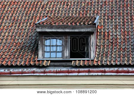 Windows in attic on old tiled roof.