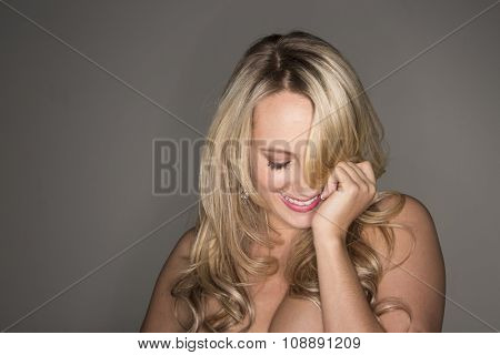 A beautiful blonde model posing in a studio environment