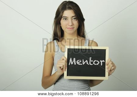 Young Woman Holding A Chalkboard Saying Mentor.