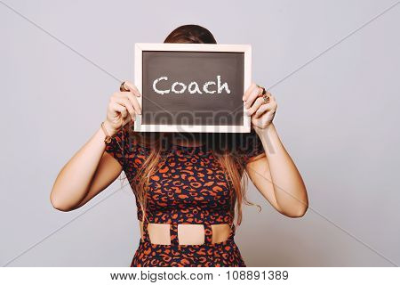 Young Woman Holding A Chalkboard Saying Coach