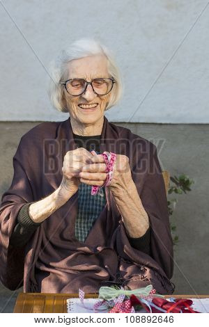 Senior Woman Making A Christmas Decoration In The Backyard