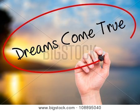 Man Hand writing Dreams Come True with black marker on visual screen.