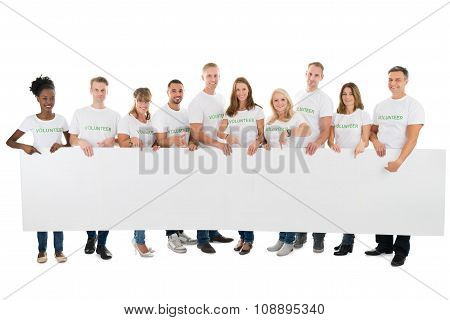 Portrait Of Confident Volunteers Holding Blank Billboard