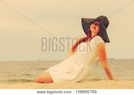redhaired happy girl in black hat on beach.
