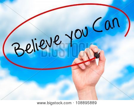 Man Hand writing Believe you Can with black marker on visual screen.