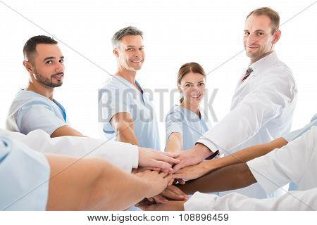 Portrait Of Smiling Medical Team Piling Hands