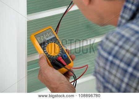 Repairman Checking Fridge With Digital Multimeter