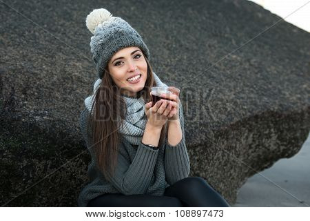 woman wearing winter clothes drinking coffee outdoors