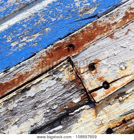 Boards of old boat with peeling paint background texture