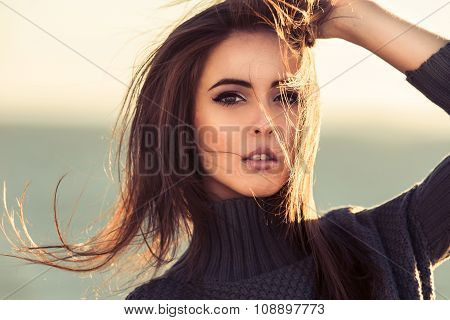 Close-up portrait of beautiful brunette woman outdoors