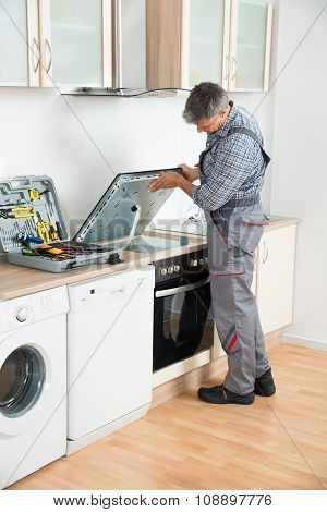 Repairman Examining Stove In Kitchen