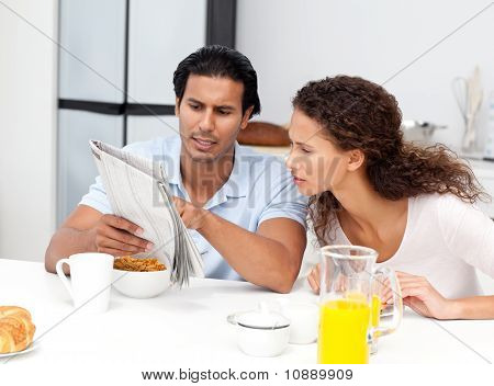 Serious Man Showing The Newspaper To His Wife During Breakfast