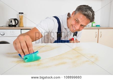 Janitor Cleaning Counter With Sponge At Home