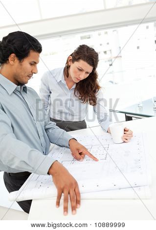 Serious Architects Looking At Plans Standing At A Table