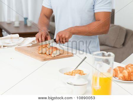 Cerca de un pan de corte del hombre durante el desayuno en su cocina
