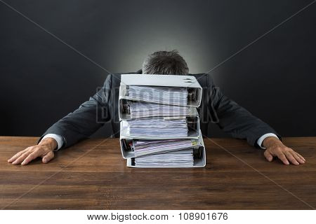 Frustrated Businessman With Lot Of Files On Desk