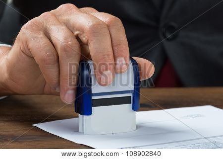 Businessman Stamping Document At Desk