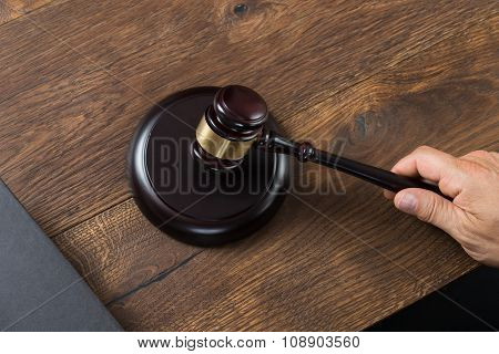 Male Judge Striking Gavel At Table