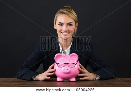 Smiling Businesswoman With Piggybank On Desk