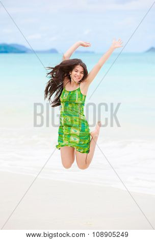 Beautiful Biracial Teen Girl Jumping In Air On Hawaiian Beach