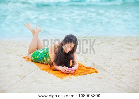 Beautiful Biracial Teen Girl Lying On Tropical Beach With Phone