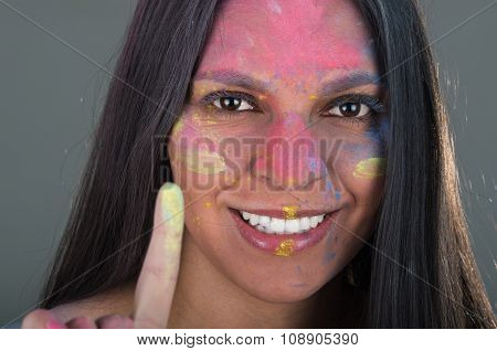 Beautiful young brunette girl painting her face with colorful powder