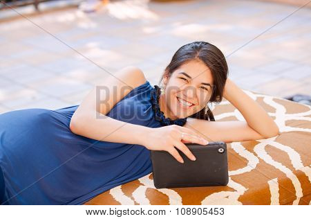Biracial Teen Girl Lying On Outdoor Bench Using Tablet Computer