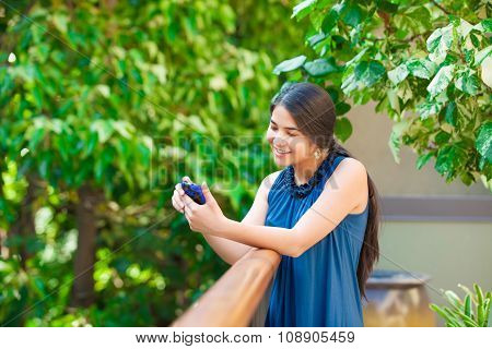 Beautiful Biracial Teen Girl Using Cellphone Outdoors By Railing