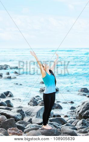 Biracial Teen Girl On Rocks By Ocean Praising God