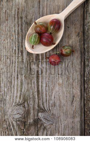 Ripe Gooseberries In A Wooden Spoon