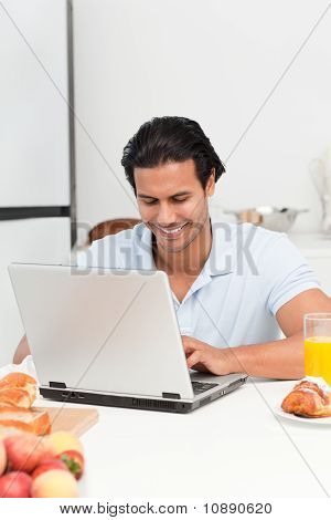 Cheerful Man Working On His Laptop During Snack Time
