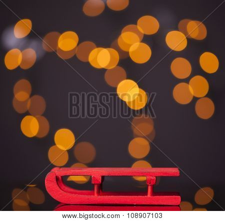 Wooden red sled on dark background