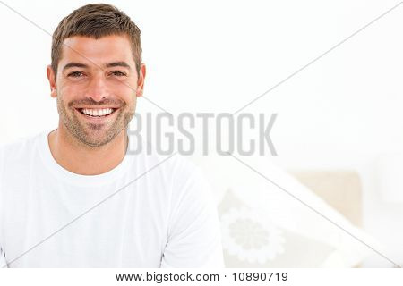 Cheerful Man Stting On His Bed At Home