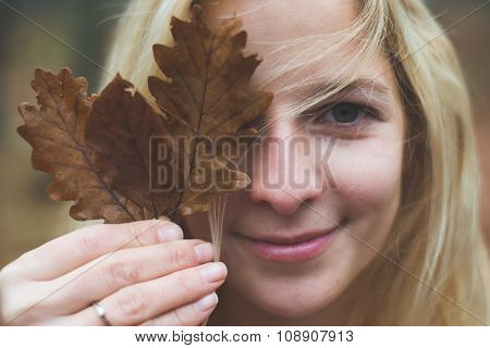 Blonde woman holding leaves in front of her face outdoor