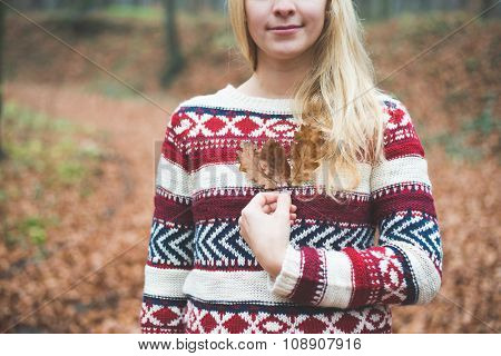 Blonde woman holding leaves outdoor