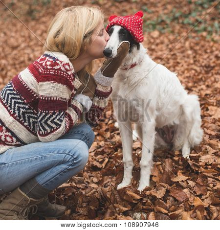 Young blonde woman embraced and kissing her cute Borzoi dog outdoor