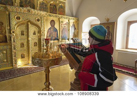 Suzdal, Russia -06.11.2015. Teen boy lighting a candle in Zachatievsky Church at Golden Ring Travel