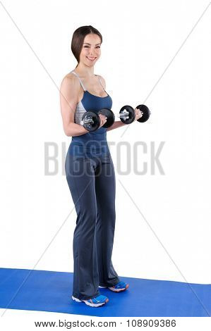 Young woman fitness instructor shows finishing position of standing dumbbell dumbbell biceps curl, isolated on white