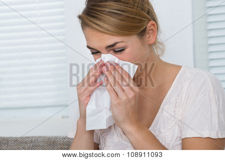 Woman Blowing Nose While Suffering From Cold