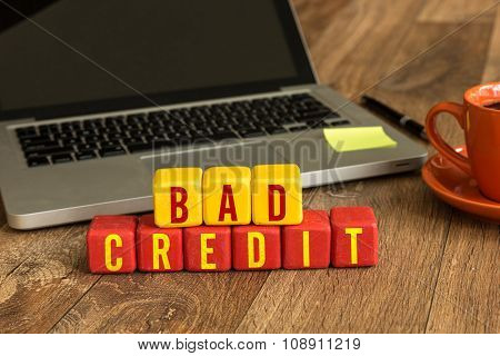 Bad Credit written on a wooden cube in a office desk