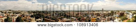 Panoramic aerial or rooftop view of thickly populated Asian city captured during afternoon