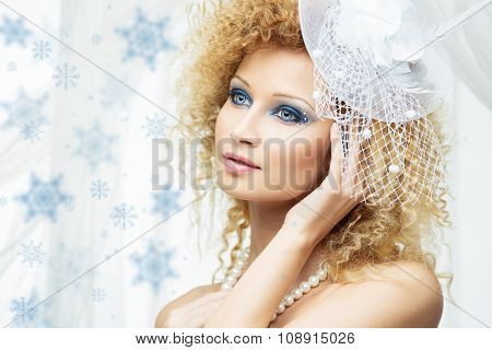 Beautiful girl with blue makeup in white hat