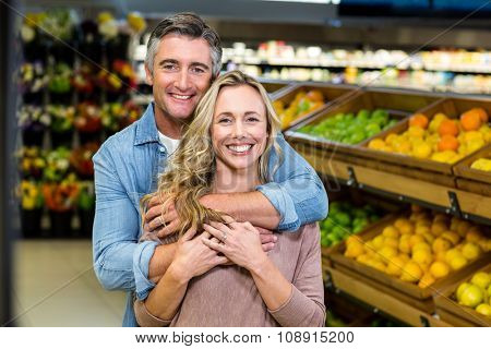 Smiling couple hugging in fruit aisle at supermarket