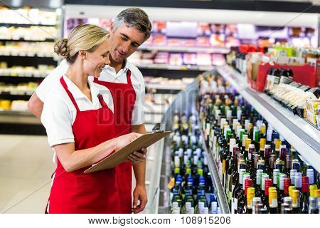 Smiling colleagues with clipboard at supermarket