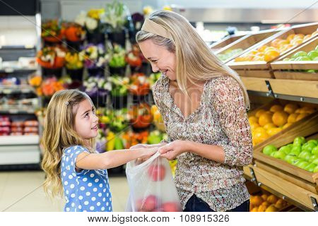 Smiling mother and daughter picking out apple in supermarket