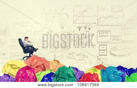 Businessman in chair and many crumpled balls of colorful paper as creativity sign